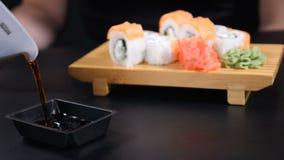 E соевый соус полит в плиту на черной предпосылке Красиво положенный набор суш на деревянной доске r сток-видео