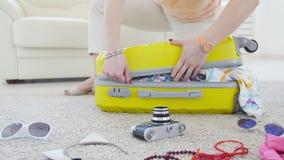 E Счастливая молодая женщина пакует красочные одежды лета в чемодан багажа для нового сток-видео