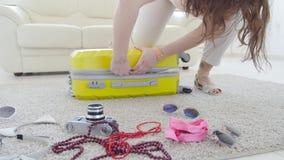 E Счастливая молодая женщина пакует красочные одежды лета в чемодан багажа для нового акции видеоматериалы