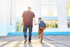 E Счастливые отец и сын идут к начальной школе стоковые фото