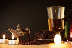 E Фонарик Рамазан с аравийской лампой, деревянным розарием, чаем, плодом дат и освещением на деревянном столе стоковые фото