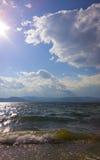 E Шторм на озере Конец шторма против предпосылки голубые облака field wispy неба природы зеленого цвета травы белое Стоковая Фотография RF