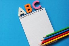 E 不同颜色笔记本和铅笔  r 库存图片