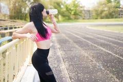 E 与拷贝空间的体育背景 运动服饮用水的年轻美女 r 库存照片