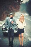 E 与有胡子的司机和豪华女孩的伴游概念减速火箭的汽车的 库存图片