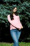 E 享用在绿色森林生活方式概念真正的女孩的年轻女人新鲜空气外面 免版税库存图片