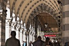 E 人们走在一个古老拱廊下 免版税库存图片
