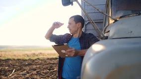E 人农夫司机站立与一种数字片剂生活方式在卡车附近 r ?? 股票视频