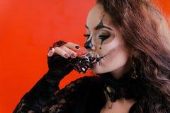 E 以头骨的形式,有长的黑发的一个深色的女孩在一件黑礼服喝从玻璃的血淋淋的液体 库存图片