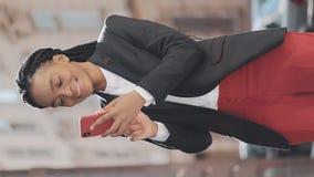 E 使用智能手机的时髦的非裔美国人的女实业家站立在街道上在商业中心附近 股票视频
