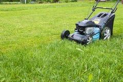 E 在绿草的割草机 刈草机草设备 割的花匠关心工作工具关闭看法晴天 库存图片