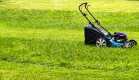 E 在绿草的割草机 刈草机草设备 割的花匠关心工作工具 关闭视图 晴朗的日 库存照片
