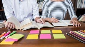 E 坐在有帮助朋友做的图书馆里的两个高中生或同学小组 库存图片