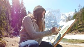 E 坐河的海岸和画绘画的一被启发的年轻女人 股票录像