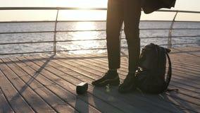 E ?? 太阳镜和棕色外套的时髦的年轻人在木散步来了,投入了音乐报告人 股票视频