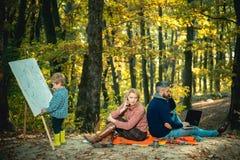 E E 妈妈和爸爸工作公园,当孩子绘画时 放松和爱好概念 工作和 图库摄影