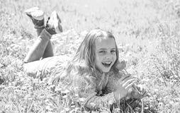 E 孩子享受春天好日子,当说谎在有雏菊花的时草甸 笑容举行的女孩 免版税库存图片