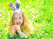 E 孩子享受春天晴朗的天气,当说谎在有嫩雏菊的时草甸 库存图片