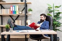E 小企业业主  人有胡子的商人坐办公室读的业务报告 分析财政 免版税库存图片