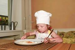 E 小女孩吃火腿和鸡蛋 逗人喜爱的女孩穿白色厨师服装 家庭和童年concep 库存照片