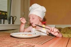 E 小女孩吃火腿和鸡蛋 逗人喜爱的女孩穿白色厨师服装 家庭和童年concep 免版税库存照片