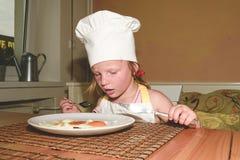 E 小女孩吃火腿和鸡蛋 逗人喜爱的女孩穿白色厨师服装 家庭和童年concep 库存图片