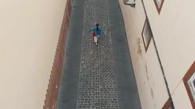 E 年轻女人沿老镇的一条狭窄的街道大加那利岛,a海岛的首都的走  影视素材