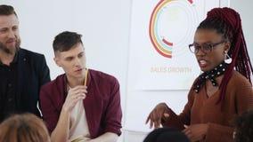 E 愉快的年轻非洲上司女商人谈论工作与不同的办公室同事 股票录像