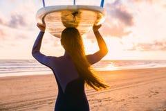 E 有冲浪板的妇女在日落或日出的一个海滩 冲浪者和海洋 免版税图库摄影