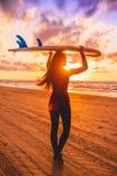 E 有冲浪板的少妇在日落的一个海滩 图库摄影