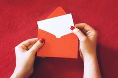 E 有空的卡片的女性手和在红色背景的红色信封 库存照片