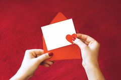 E 有空的卡片的女性手和在红色背景的红色信封 免版税图库摄影