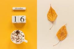 E 木日历10月16日,杯子可可粉用蛋白软糖和在黄色米黄背景的黄色秋叶 库存图片