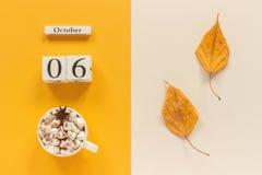 E 木日历10月6日,杯子可可粉用蛋白软糖和在黄色米黄背景的黄色秋叶 免版税图库摄影
