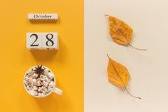 E 木日历10月28日,杯子可可粉用蛋白软糖和在黄色米黄背景的黄色秋叶 免版税库存图片