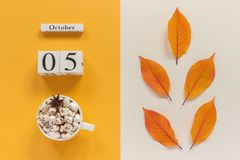 E 木日历10月5日,杯子可可粉用蛋白软糖和在黄色米黄背景的黄色秋叶 库存图片