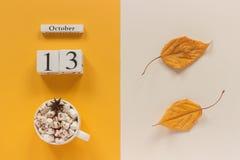 E 木日历10月13日,杯子可可粉用蛋白软糖和在黄色米黄背景的黄色秋叶 库存图片