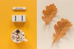 E 木日历10月11日,杯子可可粉用蛋白软糖和在黄色米黄背景的黄色秋叶 免版税库存图片