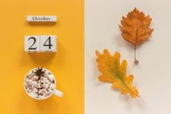 E 木日历10月24日,杯子可可粉用蛋白软糖和在黄色米黄背景的黄色秋叶 免版税库存图片