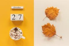 E 木日历10月27日,杯子可可粉用蛋白软糖和在黄色米黄背景的黄色秋叶 免版税库存图片