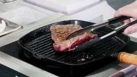 E 油煎牛排未加工的片断在平底锅的和它移交的厨师 影视素材