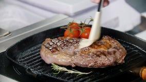 E 油煎牛排的片断在平底锅的厨师 用刷子摩擦汁液 影视素材