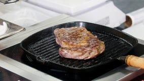 E 油煎牛排的片断在平底锅的厨师 股票视频