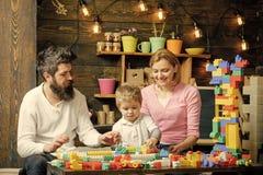 E 父亲、母亲和逗人喜爱的儿子使用与建设者砖 在繁忙的面孔的家庭一起花费时间  免版税库存照片