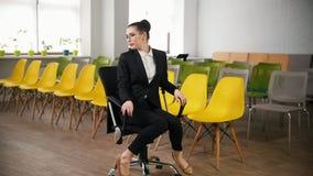 E 玻璃的一名妇女在转动在椅子的商业中心 影视素材