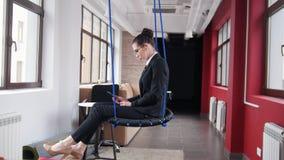 E 玻璃的一名妇女坐摇摆在办公室和听音乐 影视素材