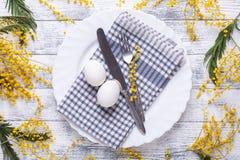 E 白鸡蛋,在板材的餐巾,含羞草花,叉子,在一张木桌上的刀子 图库摄影