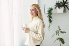 E 看在窗口的成熟妇女 免版税图库摄影