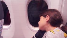 E 睡觉在飞机的年轻女孩坐由窗口 在夜生活方式的飞行 股票视频