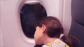 E 睡觉在飞机的年轻女孩坐由窗口 飞行在生活方式晚上 股票录像